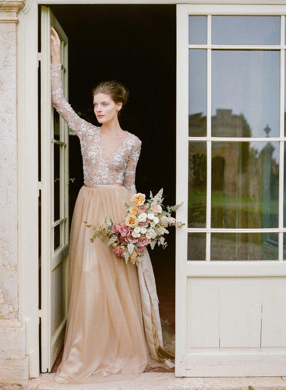 beżowa suknia ślubna z głębokim dekoltem, bukiet ze świeżych kwiatów