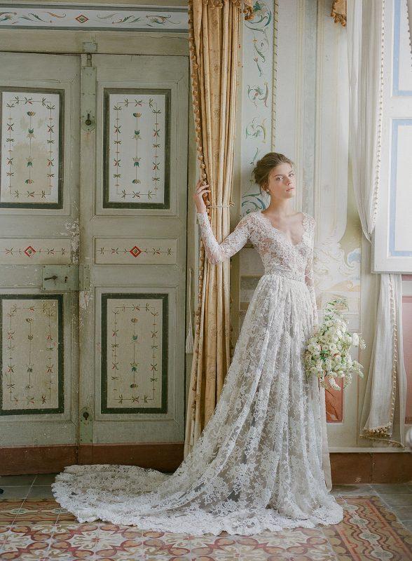 Długa koronkowa suknia ślubna z głębokim dekoltem, bukiet ślubny z naturalnych białych kwiatów