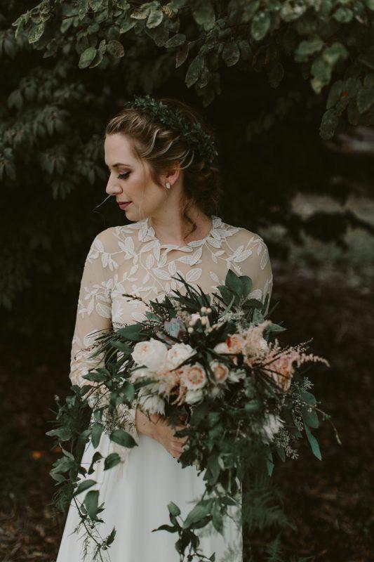 suknia ślubna z koronkowymi akcentami, zielony bukiet ślubny