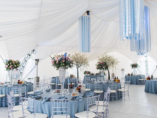 Aranżacja sali weselnej w kolorze niebieskim i białym, żywe kwiaty cięte w wazonach