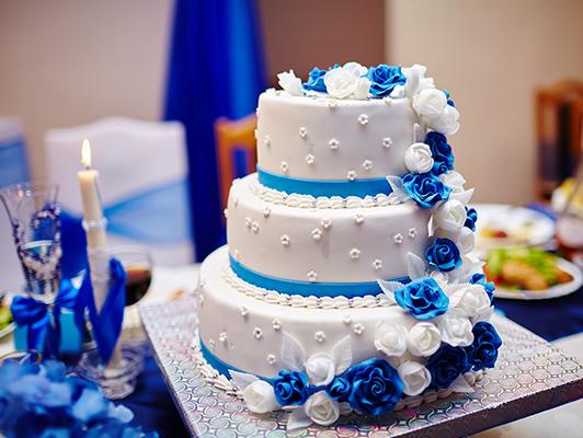tort weselny z niebieskimi akcentami, cukrowe róże w kolorze niebieskim i białym